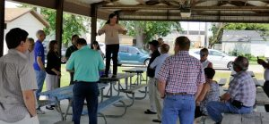 Becky McCray standing on a picnic table to speak with a group in an outdoor gathering