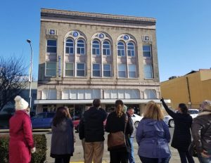 Becky McCray points out details on a downtown building to a group of people